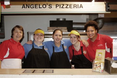 The female staff of Angelo's Pizzeria stand in a line behind the counter, smiling at the camera. The first woman has short brown hair and wears a red polo and white apron. The second, Brianna, is wearing a yellow hat, blue polo, and black apron. The third has her hair pulled back and is wearing a blue polo and black apron. The fourth is wearing a yellow hat, red polo, and black apron. And the fifth and final woman has curly brown hair and is wearing a red polo and white apron.
