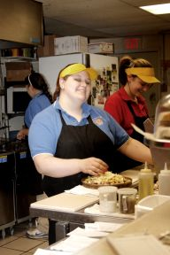 Brianna is a smiling young woman making pizza in a kitchen with two other ladies. She is wearing a yellow hat, blue shirt, and a black apron, and is putting cheese on a personal pan pizza for Roger.