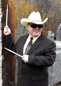Roger is smiling, standing outside by a rock wall and holding drumsticks. He is wearing a white cowboy hat and dark glasses, a black suit jacket, tie, and white button-up shirt.