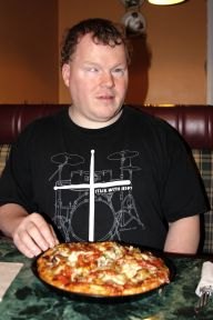 Roger enjoying a personal pizza. He is wearing a black shirt with crossed white drumsticks on it, and sitting in a plaid upholstered booth at Angelo's.