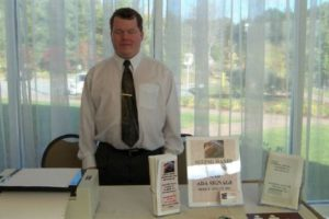 Roger is at a trade show, standing behind a table set with a printer, a small stack of brochures, a sign for Seeing Hands, and another small stack of booklets. He is wearing a white buttonup shirt and dark tie with a gold tie clip.