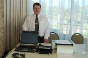Roger is standing behind a white table set with a laptop and a few other pieces of adaptive electronics. He is wearing a white buttonup shirt and and dark colored tie with a gold clip. There is a window behind him overlooking a walkway and lots of greenery.