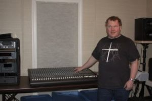 Roger stands in Studio C, near a Mackie 24-8 recording console. He is wearing a black shirt with a white cross on the front, and a silver wristwatch.