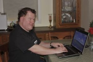 Roger sits at a table with an open laptop in front of him. He is wearing a black shirt and has a watch on his wrist.