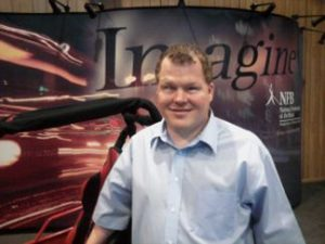 "Roger stands in front of a black framed and red upholstered dune buggy. He is wearing a blue button-up shirt. There is a poster behind him depicting moving light on one side, with the word ""Imagine"" in large font across the top, and the NFB's logo on the left side."