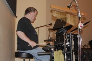 Roger sits behind an electronic drum set in a tan colored room. He is wearing a black shirt and jeans.